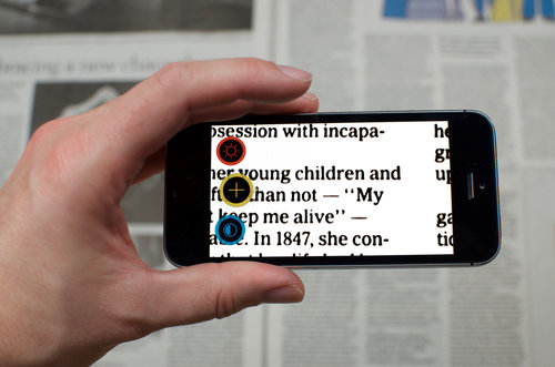 Smartphone che ingrandisce una pagina di giornale
