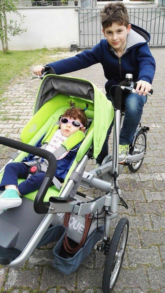 Bambino in bicicletta collegata a passeggino con bambina
