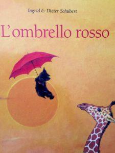 Immagine di un cane che vola appeso ad un ombrello rosso e giraffa che lo guarda