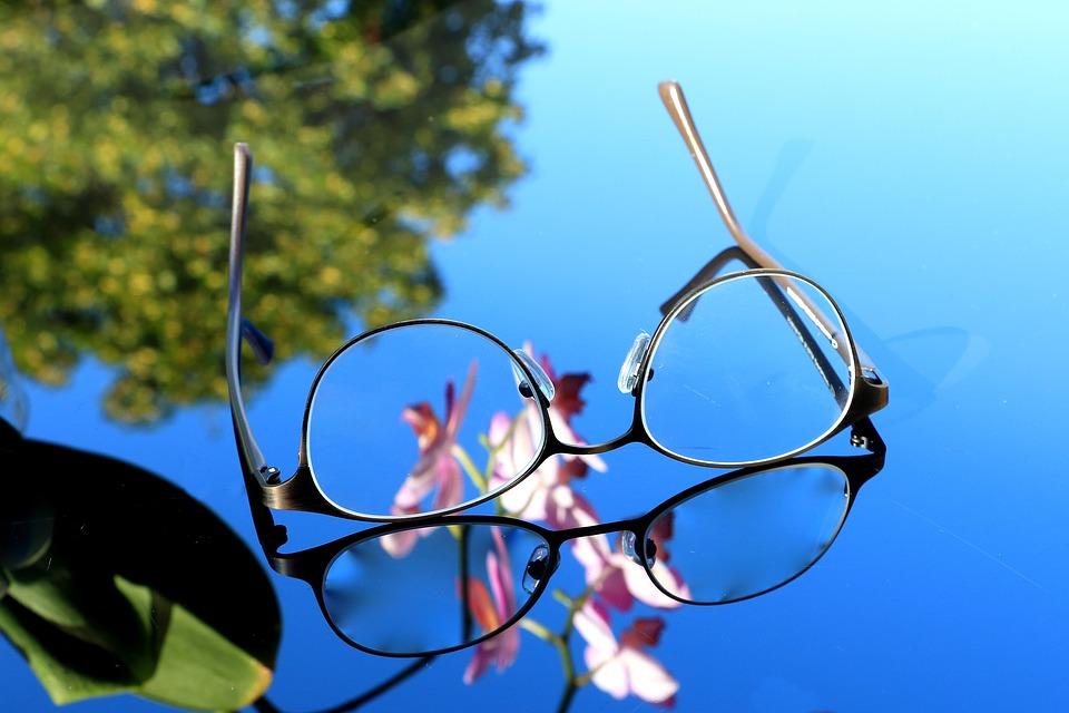 Occhiali su uno specchio che riflette cielo e un albero