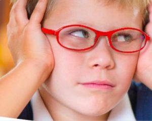 Bambino con occhiali rossi che si tiene la testa con le mani