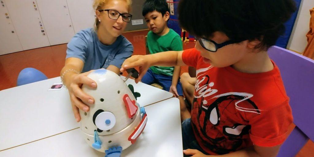 Bambini che giocano con giochi inclusivi: faccia di plastica in cui inserire occhi, naso, bocca