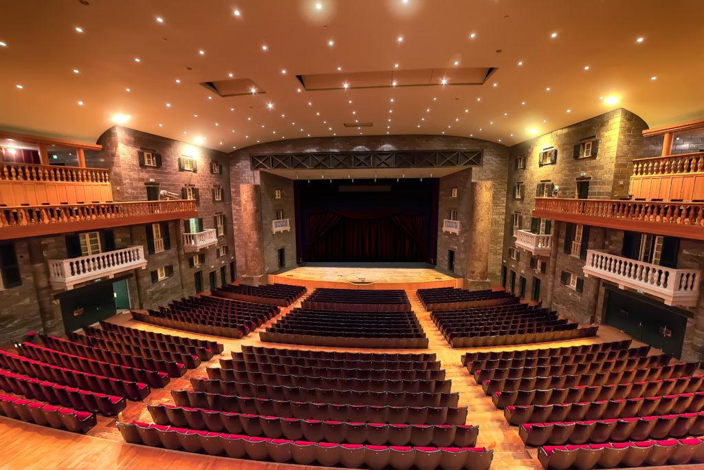Sla di un teatro con vista sul palco e poltrone