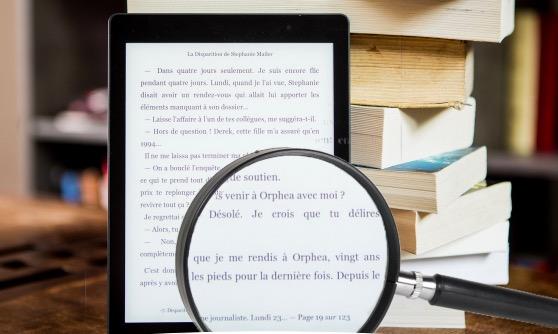 Lente di ingrandimento che ingrandisce un e-book reader, libri sullo sfondo