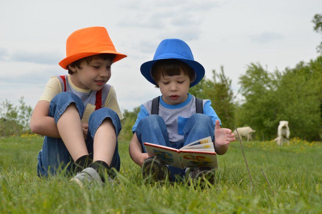 Due bambini che leggono in un prato