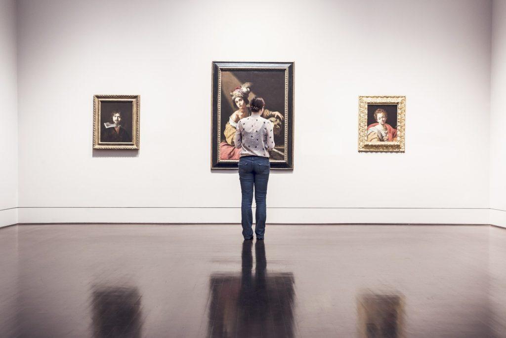 Persona che guarda un quadro in un museo
